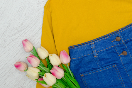 Fashion concept. Yellow sweater, blue skirt and pink tulips. Foto de archivo