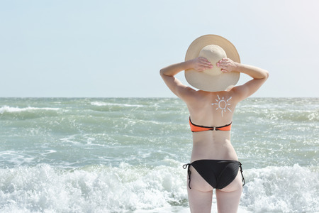 Girl in a hat and a swimsuit by the sea. Back view. Picture of the sun on the back