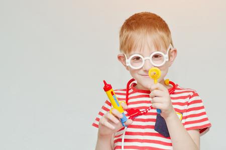 Mischievous boy playing doctor. Toy syringe, glasses and phonendoscope. Portrait Stock Photo