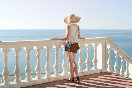 Girl in hat standing on the stairs and looking at the sea. Back view Stock Photo