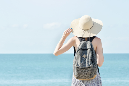 Girl in a hat standing on the coastline. Back view