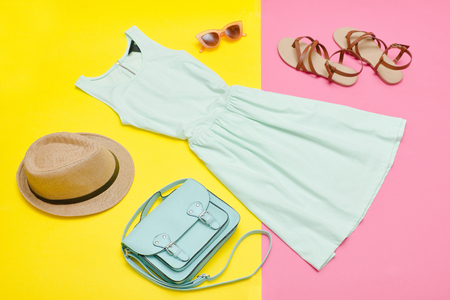 Female wardrobe. Mint dress, handbag, shoes and a hat. Bright pink-yellow background. Fashion concept