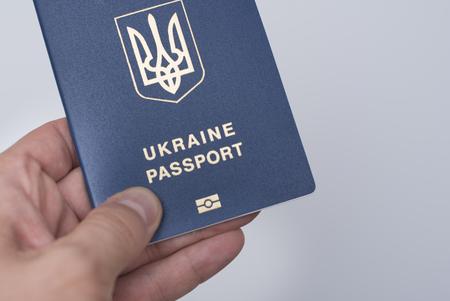 Blue Ukrainian passport in a man's hand. White background