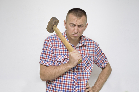 Indignant man with a sledgehammer on a white background. Work concept Stock Photo