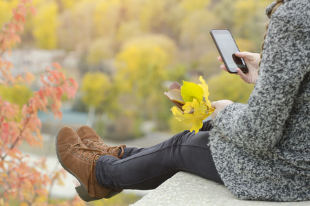 Girl with a phone sits on a hill, yellow leaves in her hand. Autumn on the background