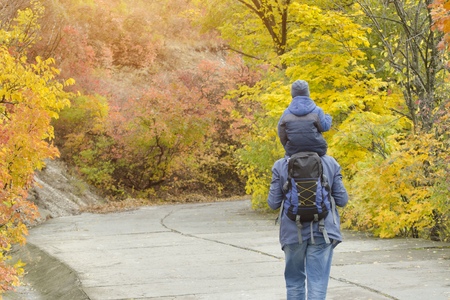 Father and son on their shoulders walk through the autumn park. Back view
