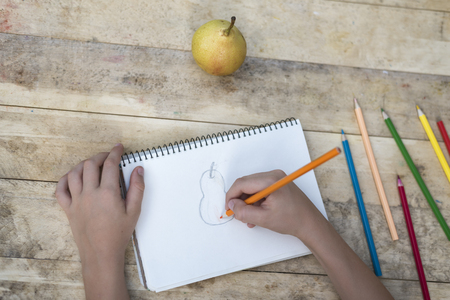 Children's hands draw a pear with colored pencils. Top view Standard-Bild