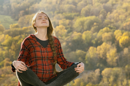 Pregnant woman sits on a hill with her eyes closed. Meditation. Autumn forest on the background