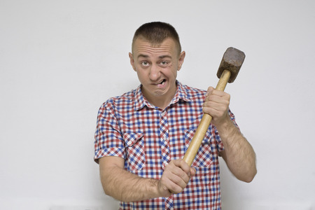Angry man with a sledgehammer on a white background. Work concept Imagens