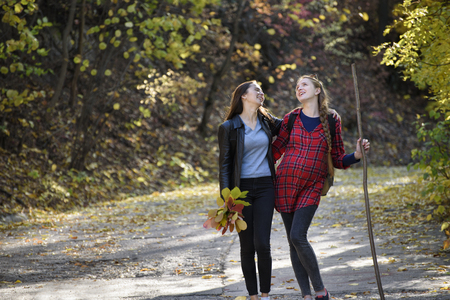 Two laughing women walk in the park. Autumn forest in the distance