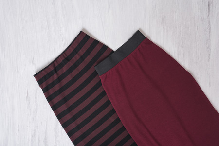Two burgundy skirts on wooden background. Fashionable concept