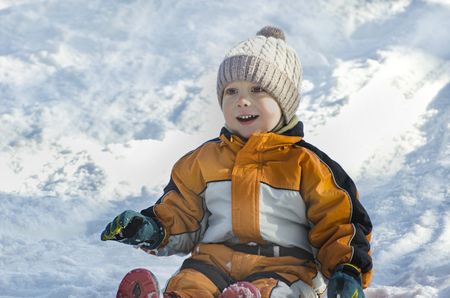 Boy in hat and orange jumpsuit slides off snow slide on back. Portrait. Close-up. Winter day