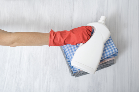 Stack of folded clothes and detergent bottle in female hand. Housework 版權商用圖片