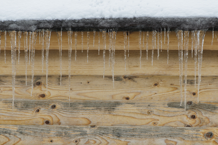Icicles on a background of brown wooden wall. Front view. Space for text.