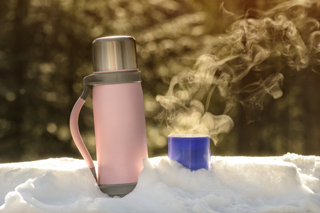 Flusk with a steaming mug of hot drink stands in the snow. Winter sunny day. 免版税图像