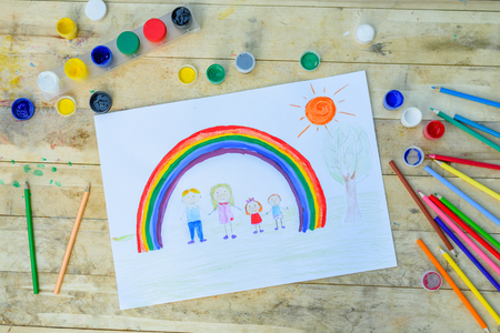 Happy family concept. Drawing on wooden table: father, mother, boy and girl hold hands against background of rainbow and sunny sky