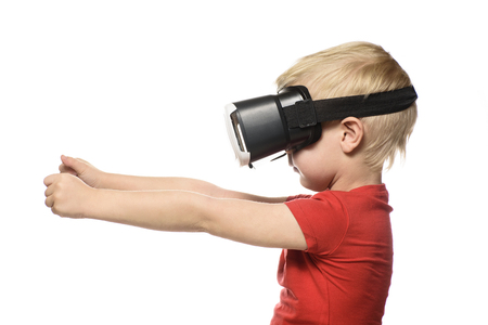Little boy in a red shirt is experiencing virtual reality holding hands in front of him. Isolate on white background. Technology concept.