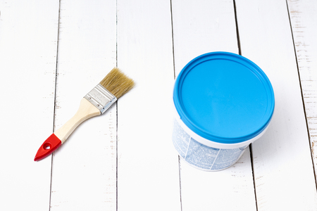 House renovation concept. Brush and a paint bucket on a background of white, shabby wooden planks Standard-Bild - 116339848