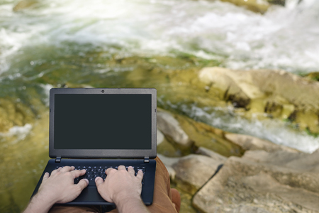 Work in nature concept. Mens hands on the laptop keyboard on the background of a mountain river. Place for text on the screen Stok Fotoğraf