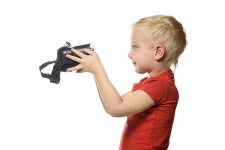 Little boy in a red shirt holds a virtual reality. Isolate on white background. Technology concept.