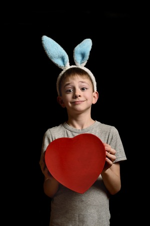 Funny blond boy in hare ears holds heart shape red box on black background. Love and family concept. Vertical frame.