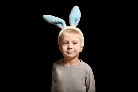 Cute little blond boy in the hare's ears standing on a black background. Portrait. Copy space.
