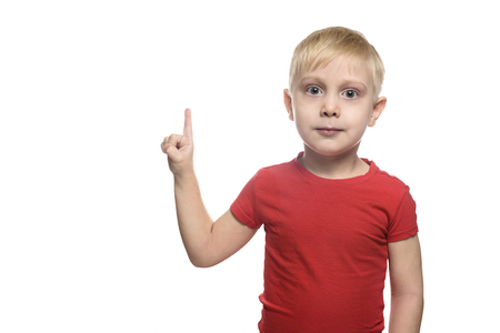 Blond boy in a red T-shirt is standing and pointing with his index finger upwards. Isolate on white background
