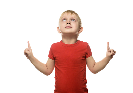 Blond boy in a red T-shirt is standing and pointing with his index fingers upwards. Isolate on white background Imagens