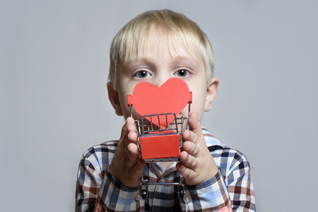 Blond little boy holding a metal shopping trolley with a heart shaped postcard inside.