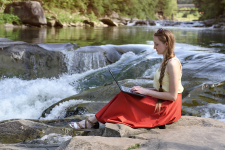 Beautiful long-haired girl in red skirt with laptop sitting on a rock on a background of mountain river cascade. Freelance concept. Work in nature. 版權商用圖片