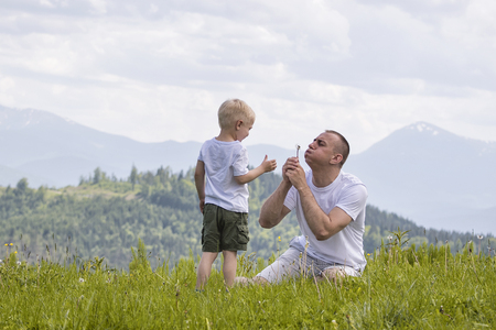 Father and young son are blowing dandelions sitting in the grass on a background of green forest, mountains and sky with clouds. Friendship concept. Stock fotó