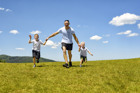 Father with two young children running hand in hand on the green field on a background of blue sky and clouds. Fatherhood and friendship. Stockfoto