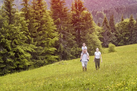 Happy family: father with son on shoulders and mother go on a green field on a background of pine forest.