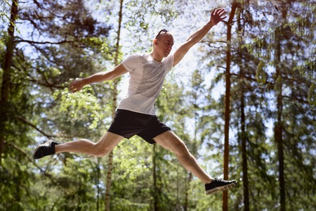 Young man jumps on a rock in a coniferous forest. Active extreme tourism.