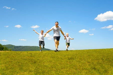 Father with two young children running hand in hand on the green field on a background of blue sky and clouds. Fatherhood and friendship. Фото со стока
