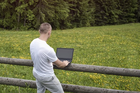 Man standing near the wooden fence in the field and works at a laptop near the pine forest.