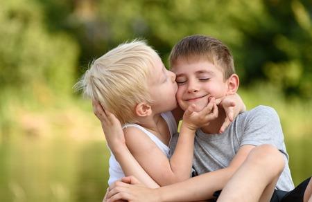 Deux petits frères sont assis dehors. L'un embrasse l'autre sur la joue. Arbres verts flous au loin. Concept d'amitié et de fraternité Banque d'images