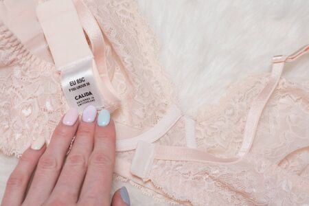 KHARKOV, UKRAINE - MARCH 04, 2019: Label CALIDA of peach bodice in female hand. Lingerie concept. Close up