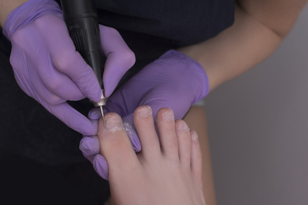 Processing toenails, pedicure. Gloved hands with a pedicure cutter. Close-up Stock Photo