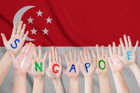 Singapore inscription on the childrens hands against the background of a waving flag of the Singapore.