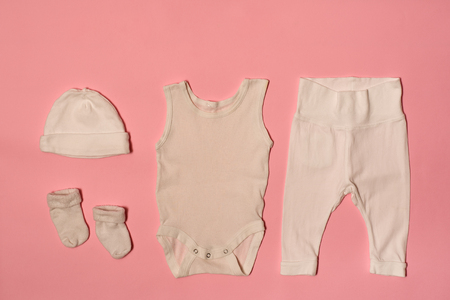Baby fashion concept on a pink background. Cap, bodysuit, pants and socks. Banque d'images