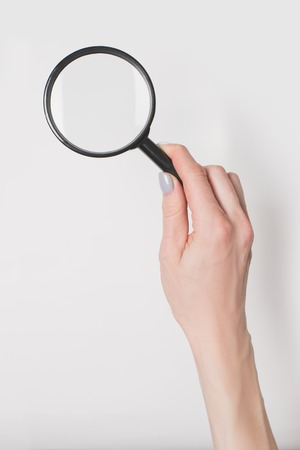 Female hand holding magnifier isolate on light background