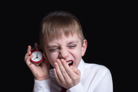 Yawning schoolboy with a red alarm clock in his hands. Morning concept. Black background Foto de archivo