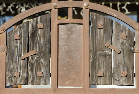 Vintage metal gates with shabby wooden board inserts. Stock Photo