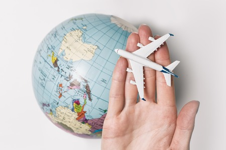 Passenger aircraft on the female palm on the background of the globe. Concept of air travel on a light background.