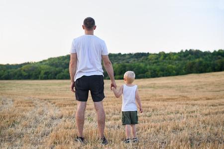 Padre con un hijo pequeño están de pie sobre un campo de trigo segado. Vista trasera. Hora del atardecer.