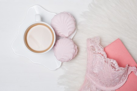 Cup of coffee with marshmallows. Pink lace bodice and notepad on white background. Fashionable concept.