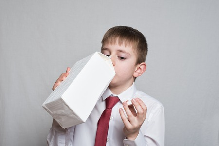 Little boy drinks from a large white package. White shirt and red tie. Light background. Archivio Fotografico - 121168469