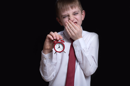 Yawning schoolboy with a red alarm clock in his hands. Morning concept. Black background