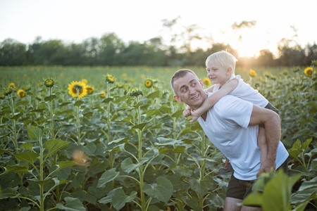 Happy smiling father with son on his back walks on the green field of blooming sunflowers at sunset. Banque d'images